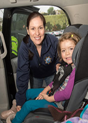 CHP officer installing child safety seat
